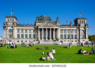 Germany, Berlin: People residents tourists in public park in front of famous parliament building Deutscher Bundestag former Reichstag in the center of the German capital with blue sky. April 21, 2018