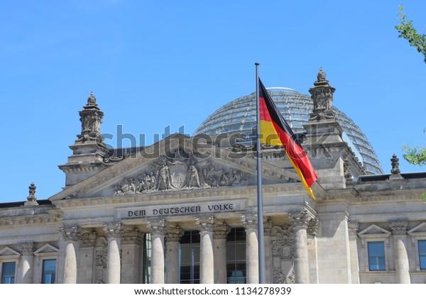 """GERMANY, BERLIN, PLATZ DER REPUBLIK - JUNE 08, 2018: Glas dome, inscription """"DEM DEUTSCHEN VOLKE"""" and German flag at Reichstag building in Berlin"""