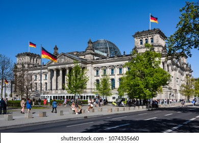 Germany, Berlin: Street scene with famous parliament building Deutscher Bundestag (former Reichstag) with national flags, cars, people, green trees in the center of the German capital. April 21, 2018