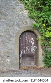 GERMANY, BIELEFELD-AUGUST 10, 2018: Oval wooden door in the fortress wall ,entwined with ivy.Ancient castle Sparrenburg