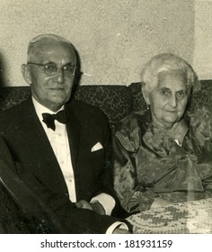 GERMANY - CIRCA 1930s: An antique photo of elegant elderly couple sitting on a sofa near the table