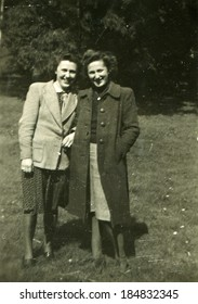 GERMANY - CIRCA 1930s: An antique photo of two young demi-season clothing women posing on meadow on a background of park