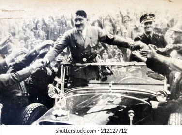 GERMANY - CIRCA 1940s: Adolf Hitler stands in a convertible and shaking hands with his fans,  Reproduction of antique photo.