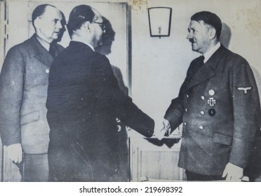 GERMANY - CIRCA 1940s: Adolf Hitler shakes hands with one of the man during an official meeting. Antique photograph.