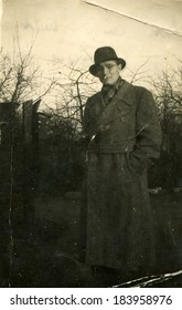 GERMANY - CIRCA 1940s: An antique photo of middle-aged man in glasses, coat and hat posing against the backdrop of autumn garden
