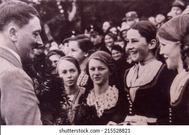 GERMANY - CIRCA 1942: Adolf Hitler talking to young girls during a meeting with his supporters. Reproduction of antique photo.