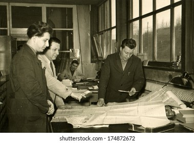 GERMANY -  CIRCA 1950s: An antique photo shows engineers in the design office discussing drawing