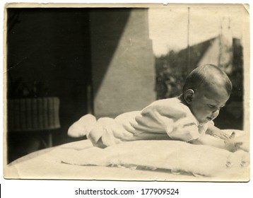 GERMANY - CIRCA 1950s: An antique photo of baby lying on his stomach on the table against the background of a private house