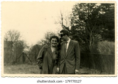 GERMANY - CIRCA 1950s: An antique photo of smiling woman in demi-season coat and a man in a business suit and wearing sunglasses posing against the backdrop of the fence and trees