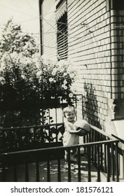 GERMANY - CIRCA 1950s: An antique photo of little girl playing with a ball in the playpen in the yard of a private brick house