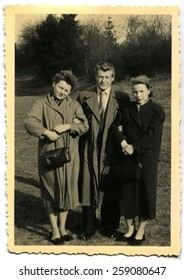 GERMANY - CIRCA 1950s: Two women and a man in a coat posing in the woods on a background of trees