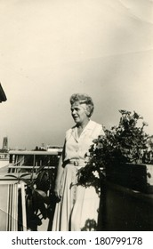 GERMANY - CIRCA 1954: An antique photo of elderly woman posing on the balcony