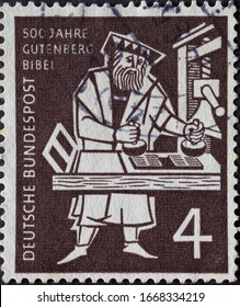 GERMANY - CIRCA 1954: On this postage stamp  Johannes Gutenberg can be seen printing the first Bible on a printing press. The stamp was published on the occasion of the 500th anniversary