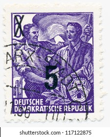 GERMANY - CIRCA 1954: A stamp printed in Germany, shows workers shaking hands under the flag (changing the nominal), series Five year plan, circa 1954