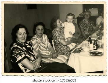 GERMANY -  CIRCA 1960s: An antique photo shows group of elderly women sitting near the festive table, one of them holding a baby on her knees