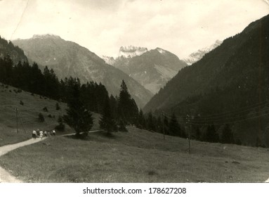 GERMANY - CIRCA 1960s: An antique photo of people are on the road in a mountain valley