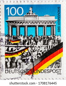 GERMANY - CIRCA 1990: a postage stamp printed in Germany showing the Brandenburg Gate with people on the Berlin Wall. Day of the Fall of the Wall November 9, 1989