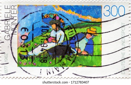 GERMANY - CIRCA 1994: a postage stamp printed in Germany showinga painting of a couple on a meadow near Murnau. Text: Gabriele Münter