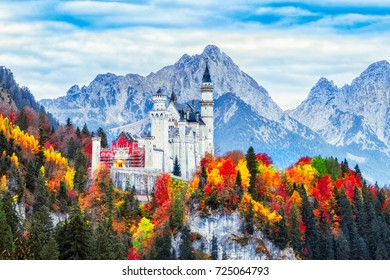Germany. Classical view on Neuschwanstein castle begirt colorful fall forest in Bavaria land. Beautiful autumn scenery. Neuschwanstein castle is famous and very popular travel destination in Europe.