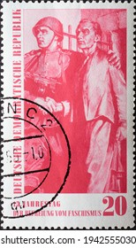 GERMANY, DDR - CIRCA 1960 : a postage stamp from Germany, GDR showing a Red Army soldier with a steel helmet supports a freed prisoner from a concentration camp. anniversary of liberation from fascism