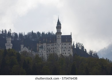 Germany. Famous Neuschwanstein Castle in the background of snowy mountains and trees with yellow and green leaves.