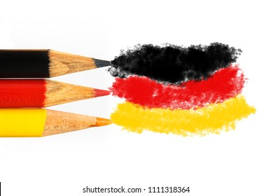 Germany flag colours in coloured pencils in black, red and gold in a closeup photo isolated on white background with space for text. Concept for Germany and learn German language, people and culture.