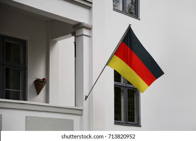 Germany flag. German flag displaying on a pole in front of the house. National flag of Germany Deutschland waving on a home hanging from a pole on a front door of a building.