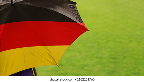 Germany flag umbrella. Close up of printed umbrella over green grass lawn / field. Rainy weather forecast concept.