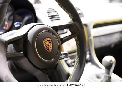 Germany, Frankfurt - 10.September 2019: Porsche 718 Cayman GT4 - detail view of steering wheel with controls and porsche company logo - Sports Car - IAA Car Show Frankfurt 2019