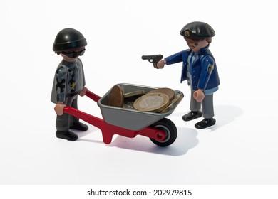 Germany, Frankfurt - June 16, 2014: Robbery scene of a Playmobil figure with a wheelbarrow containing real Euros