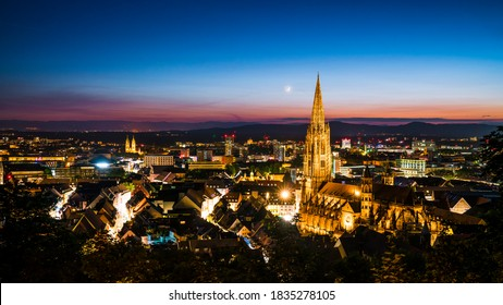 Germany, Freiburg im Breisgau, Magical blue hour atmoshpere of the illuminated skyline and minster cathedral, aerial view above with moon