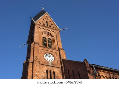 Germany, Greifswald: Steeple of local neo-Romanesque church (Bugenhagenkirche) with tower clock and blue sky.
