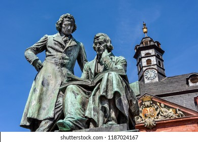 Germany, Hanau: National memorial statue of famous Grimm Brothers in the city center of the German town with town hall and blue sky in background - concept culture fairy tales art travel history