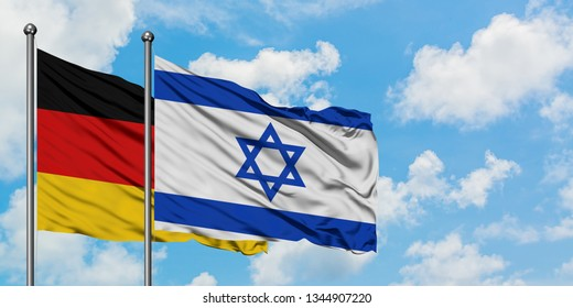 Germany and Israel flag waving in the wind against white cloudy blue sky together. Diplomacy concept, international relations.