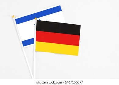 Germany and Israel stick flags on white background. High quality fabric, miniature national flag. Peaceful global concept.White floor for copy space.