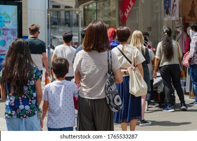Düsseldorf, Germany - JUNE 2020: Selected focus view, Group of European family queue and wait for shopping on sidewalk outside store during social distancing and quarantine regulations for COVID-19.