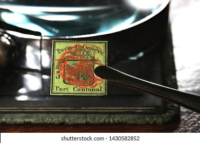 GERMANY - JUNE 8, 2019: 5 cent Geneva cantonal stamp from 1847 held by tweezers.