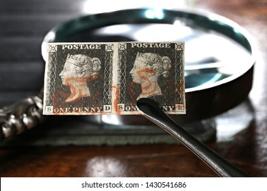 GERMANY - JUNE 9, 2019: Horizontal pair of plate 1b Penny Black with red Maltese cross cancellation held by tweezers. It is the world's first adhesive postage stamp.