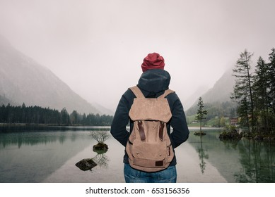 Germany. Lake Hintersee. Girl traveler with a backpack near a high mountain lake in the Alps