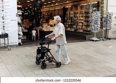 Germany, Leipzig, October 6, 2018: An elderly woman with a special cart for the elderly is walking down the street.
