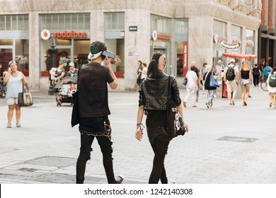 Germany, Leipzig, September 6, 2018: Young couple punks or friends walking down the street in Leipzig. He listens to music on the phone. Youth subculture.
