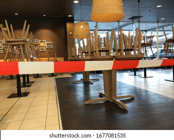 Tönisvorst, Germany - March 19. 2020: View beyond red white don´t cross line in empty closed restaurant with chairs stapled on tables during corona crisis
