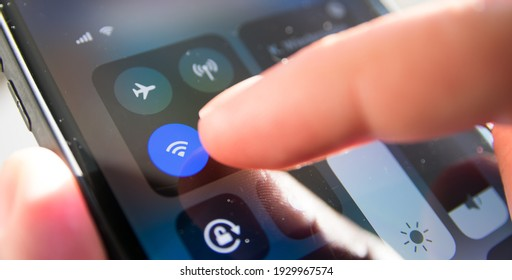 Germany - March 2021: With a smartphone with a button on the screen of a mobile device, you can connect to WiFi internet access, free, secure access to the internet for e-mail and web browsing