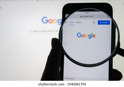 """Germany - March 21, 2021: person looking with a magnifying glass at the Google search engine from iphone. """"Google"""" is the number one search site."""