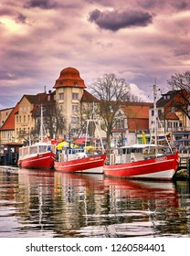 Warnemünde, Germany - March 27, 2018: Three fishing boats in Warnemünde at the old canal or old creek. The once sleepy fishing village was founded in 1200.
