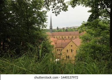 GERMANY, MAULBRONN - 22 June 2019: Maulbronn Monastery framed by green leaves