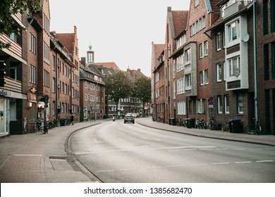 Germany, Muenster, August 17 2018: View of the city street. Bicycles are parked on the side of the road. On the road going car. Typical day.
