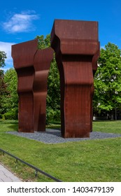 Germany, Munich: Big rusty monument sculpture in green park between Alte Pinakotek and Pinakothek der Moderne in the city center of the Bavarian capital - concept public conceptual art. May 09, 2019