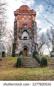 Germany, Pritzwalk, Trappenberg: Historic Bismarck tower (Bismarckturm) from below with red brick exterior wall, window, crests, battlements, observation deck and blue cloudy sky - concept monument