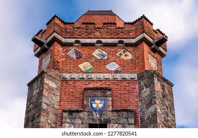 Germany, Pritzwalk, Trappenberg: Historic Bismarck tower (Bismarckturm) from below with brick exterior wall, window, old crests, battlement, observation deck and blue cloudy sky - concept monument